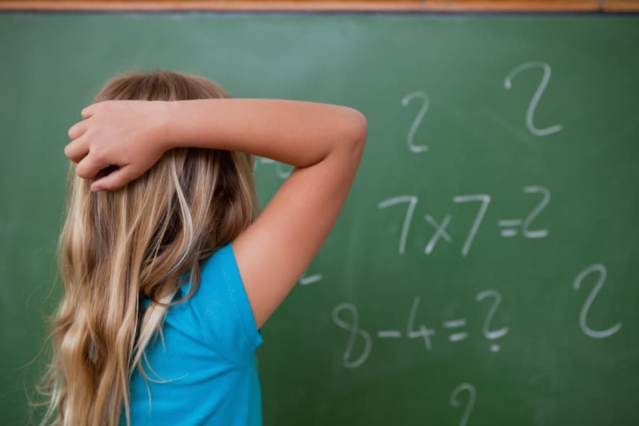 little girl standing at chalk board scratching her head